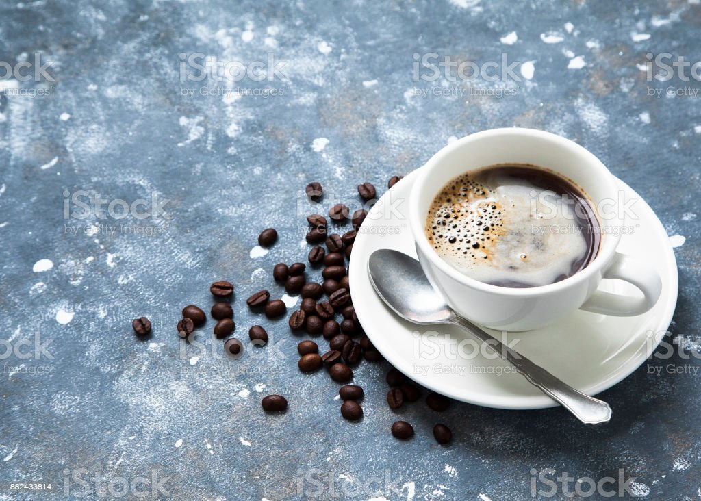 Cup of coffee on a table and beans scattered around. stock photo