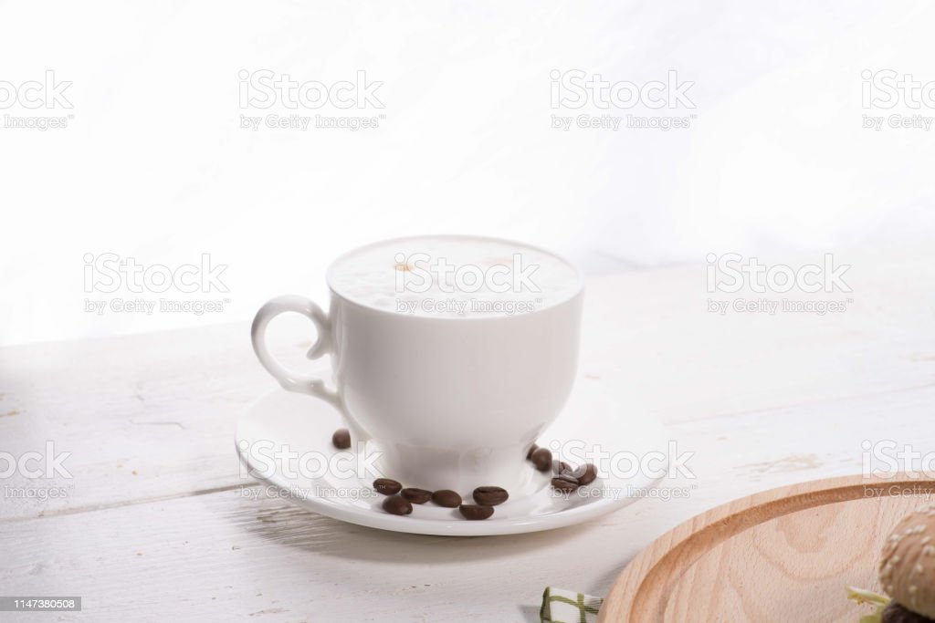 cup of coffee on a white background and scattered coffee beans on a...