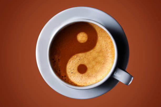 Taza de café sobre fondo negro. Imagen del yin-yang en la crema de café. vista superior. café en forma de Yin Yang vista superior - foto de stock