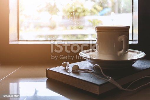 Cup of coffee on book by the window on a rainy day with soft-focus in the background. over light