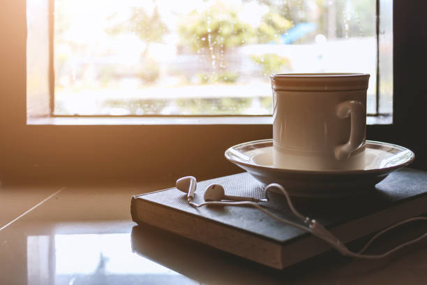 Cup of coffee on book by the window on a rainy day with soft-focus in the background. over light – zdjęcie