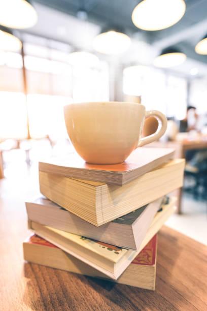 Uma xícara de café na pilha de livros sobre a mesa de café. Na época de exames de estudante de universidade em foco seletivo. - foto de acervo