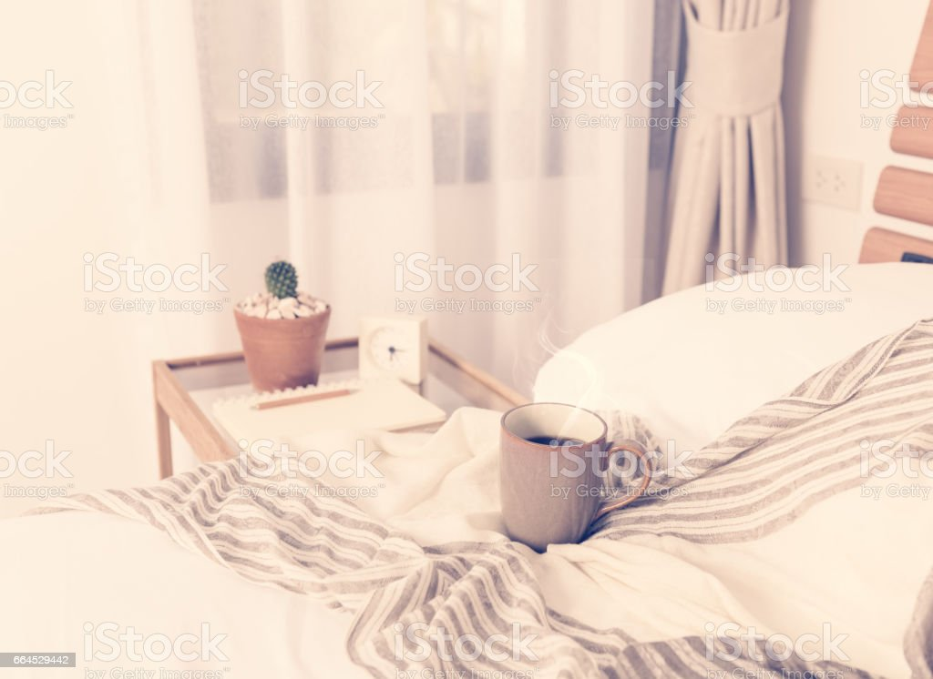 Cup of coffee on cozy white bed royalty-free stock photo