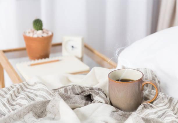 tasse kaffee auf gemütlichem weißen bett - blumenuhr stock-fotos und bilder