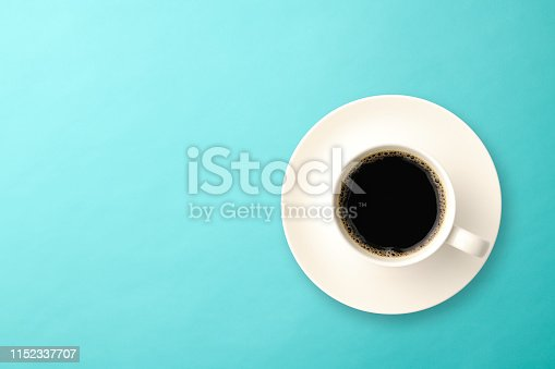 Overhead shot of a cup of coffee on light blue background with copy space.