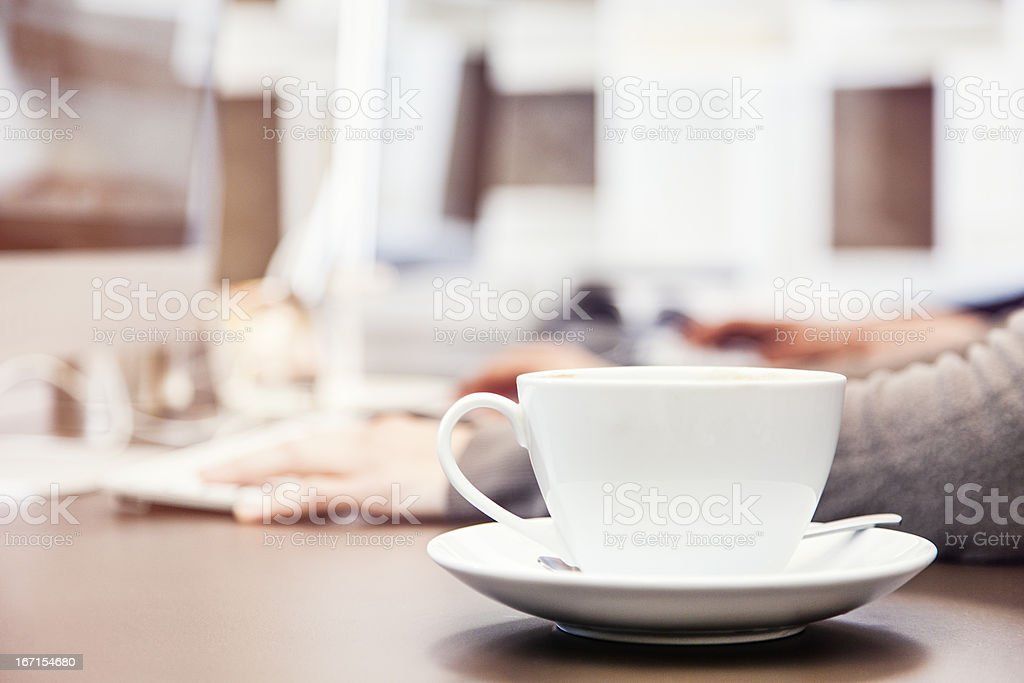 Cup of coffee on office desk stock photo
