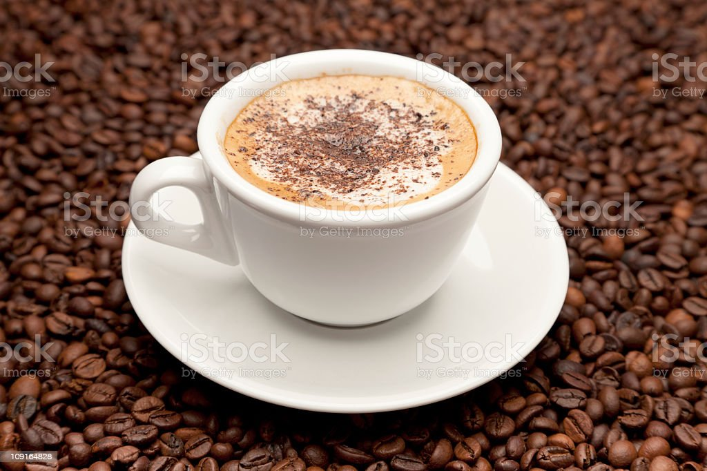 Cup of coffee (macchiato / cappuccino) on roasted coffee-beans royalty-free stock photo