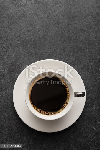Cup of coffee on gray table from above