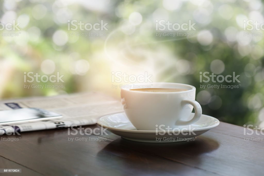 A cup of coffee on teak wood table with blurred mobile phone on newspaper