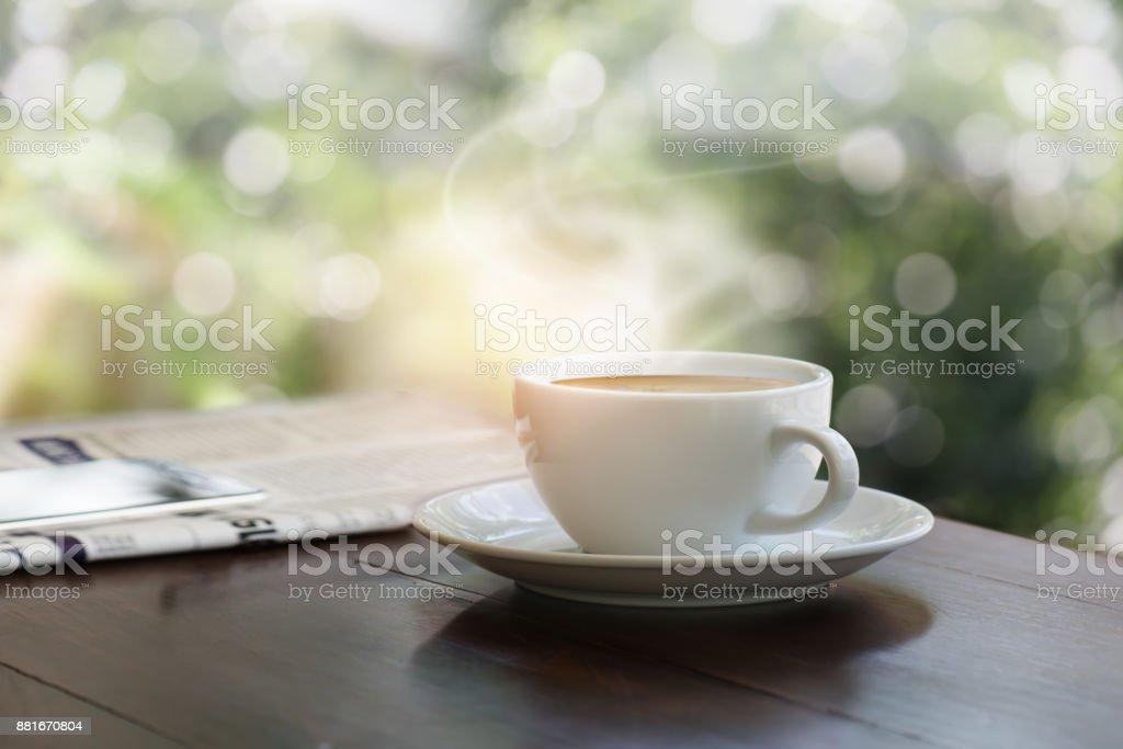 Une tasse de café sur la table en bois teck avec GSM floue sur le journal - Photo
