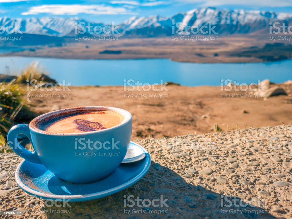 A cup of coffee on the background of snowy mountains - Zbiór zdjęć royalty-free (Brązowy)