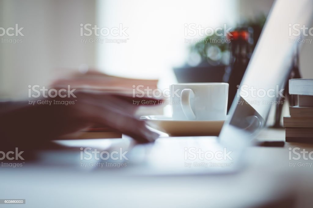 Cup of coffee on the desk in an office Cup of coffee on the desk in an office. Defocused woman's hand on the laptop keyboard. Adult Stock Photo