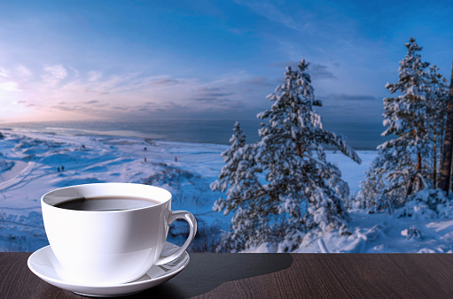 Cup of coffee on the table with view of snowy beach with dunes, Baltic sea and covered in snow fir trees on the hill.