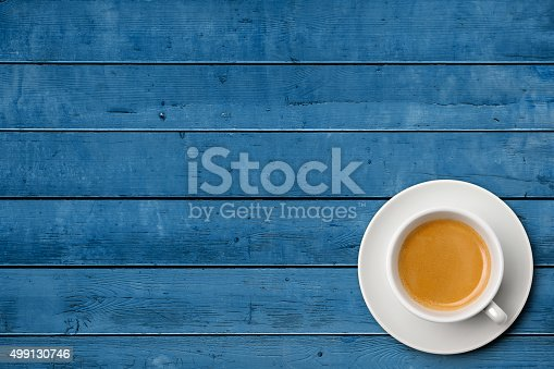 istock Cup of coffee on weathered blue table 499130746