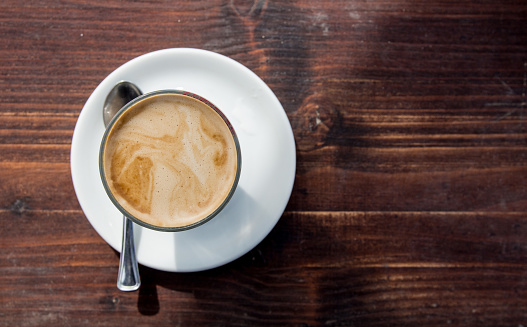 Cup of coffee on weathered brown wood table