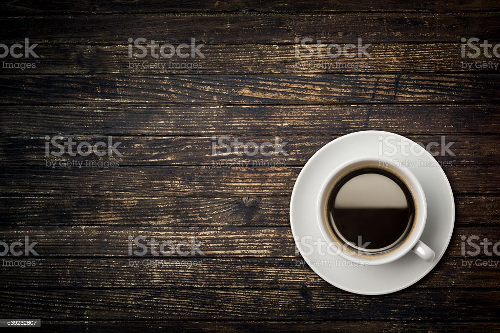 Cup of coffee on weathered dark table stock photo