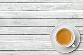 istock Cup of coffee on weathered white table 496880868