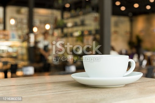 Cup of coffee on wooden table in cafe with blurred background