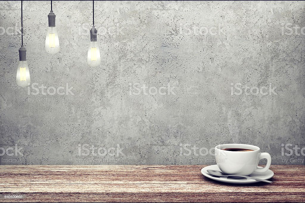 Cup of coffee on wooden table near concrete wall stock photo