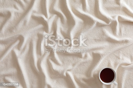 Cup of coffee or tea on beige textured background with warm plaid, copy space. Flat lay, top view