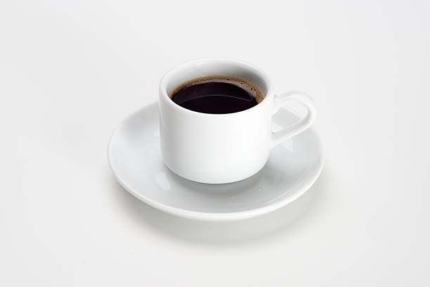 Cup of coffee over white background Black coffee with bubbles in white cup with saucer. black coffee stock pictures, royalty-free photos & images
