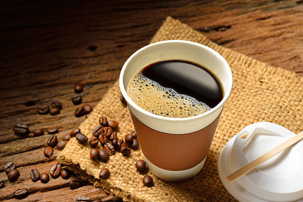 Cup of coffee Paper cup of coffee and coffee beans on wooden table disposable cup stock pictures, royalty-free photos & images