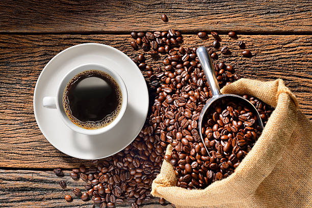 Cup of coffee Cup of coffee and coffee beans on wooden table caffeine stock pictures, royalty-free photos & images