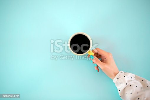 Top view of cup of coffee and human hand on a blue background. Pop art style. Minimalism.