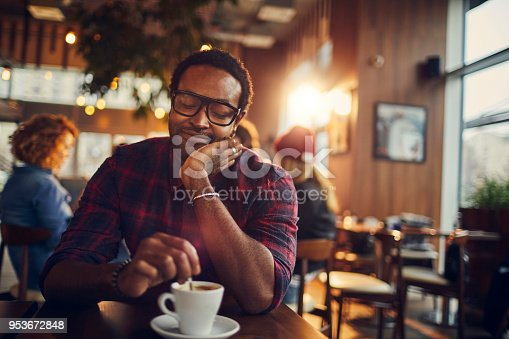 Close up of a young man having a coffee in a cafe