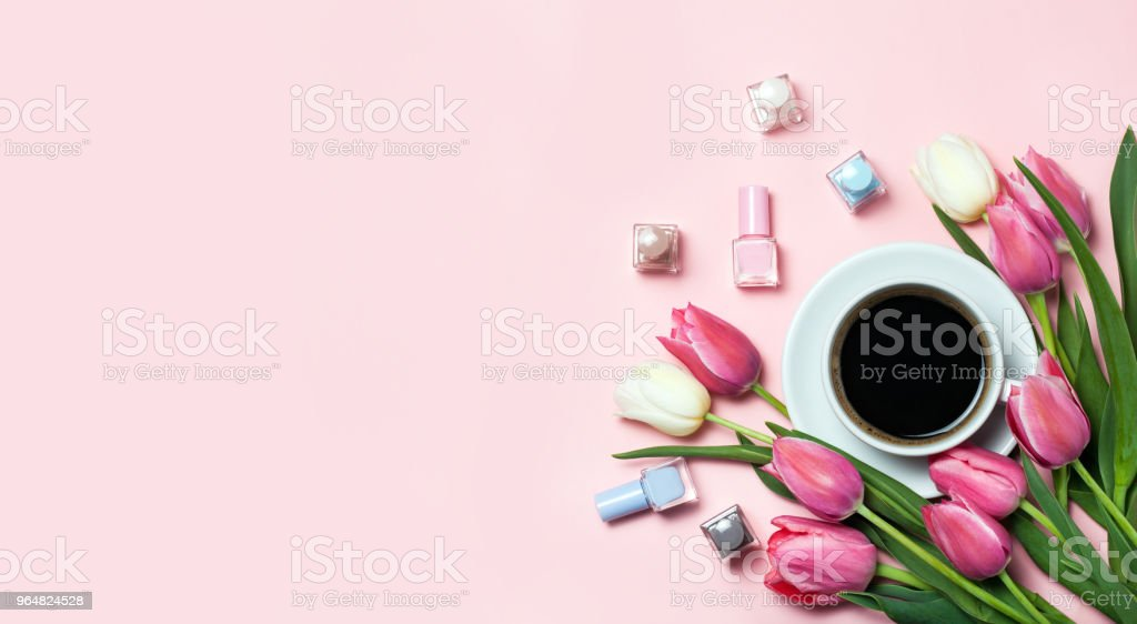 Cup of coffee, pink tulips and nail pilishes on pink background. royalty-free stock photo