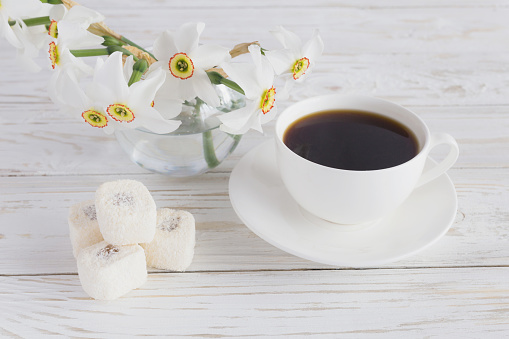 Cup of coffee, Rahat lokum with coconut and narcissus