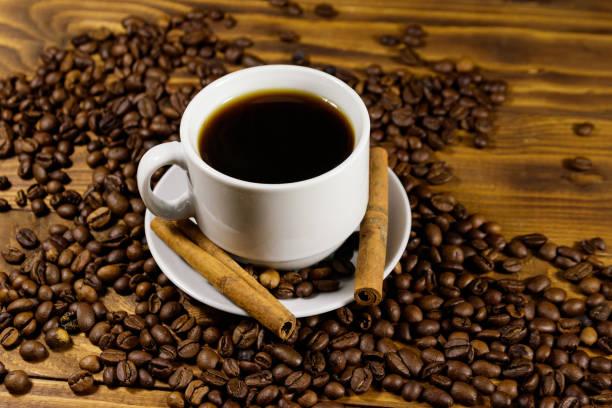 木桌上的一杯咖啡、烤咖啡豆和肉桂棒 - 咖啡 飲品 個照片及圖片檔