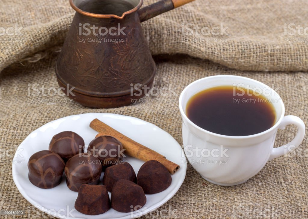 cup of coffee, saucer, truffle chocolates, cinnamon sticks,. stock photo