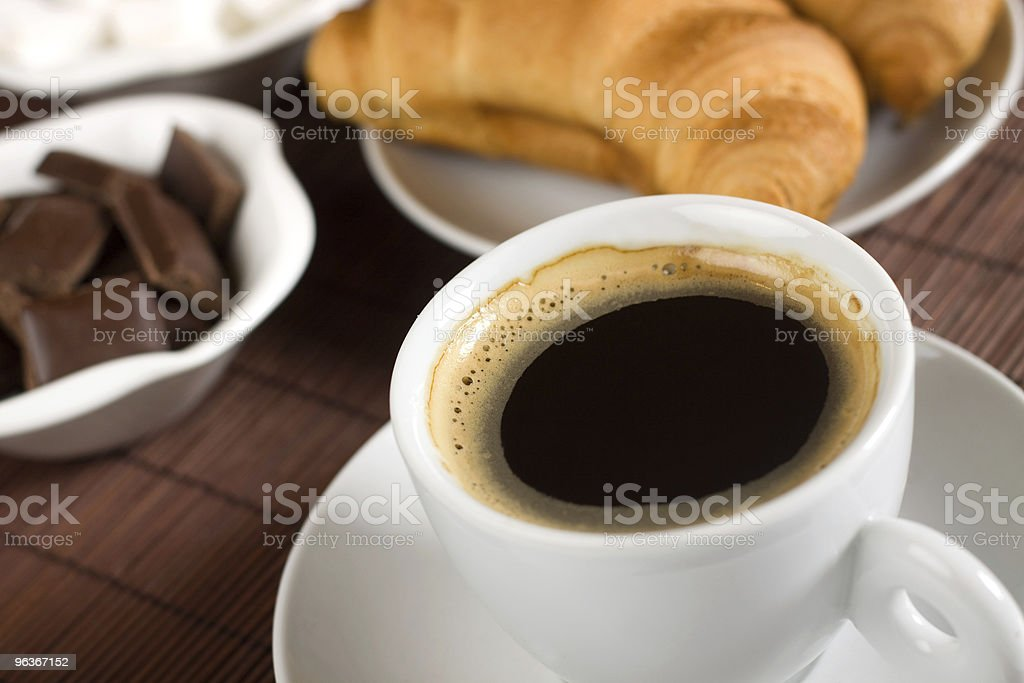 Cup of coffee served with croissants and chocolate royalty-free stock photo