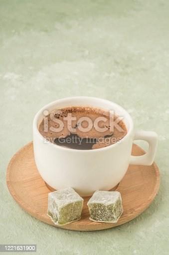 A cup of coffee served with Turkish delights on green with copy space
