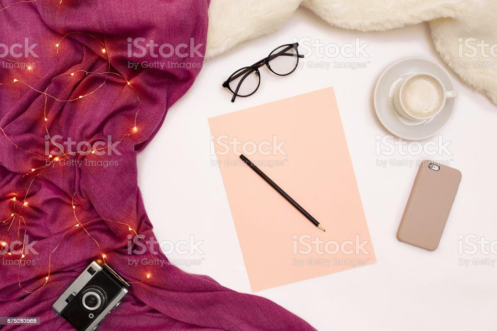 Uma xícara de café, papel inteligente, rosa, com metas de ano novo. Cachecol e Natal luzes no fundo branco - foto de acervo