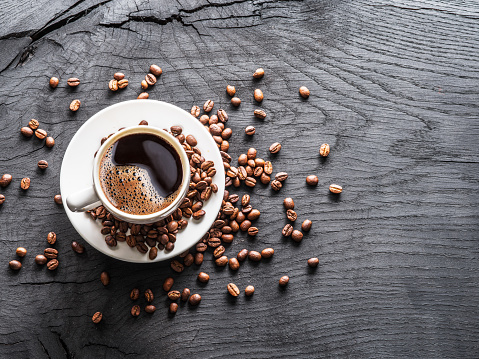 Cup of coffee surrounded by coffee beans.