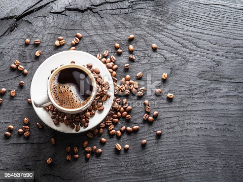 istock Cup of coffee surrounded by coffee beans. 954537590