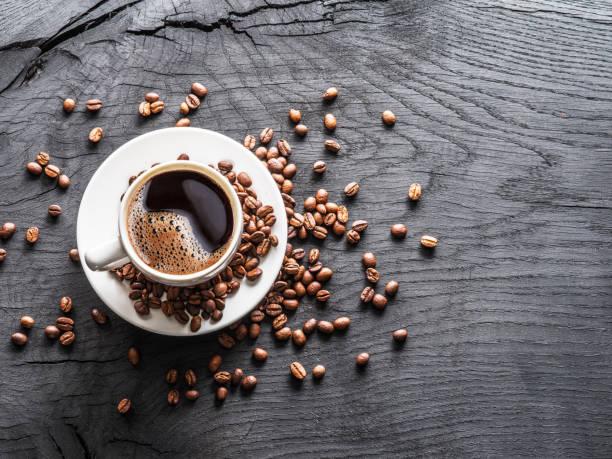 filiżanka kawy otoczona ziarnami kawy. - coffee zdjęcia i obrazy z banku zdjęć