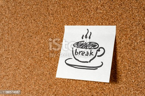 A cup of coffee / tea with the inscription break on a sticker on a cork board. Background, copy space, design element.