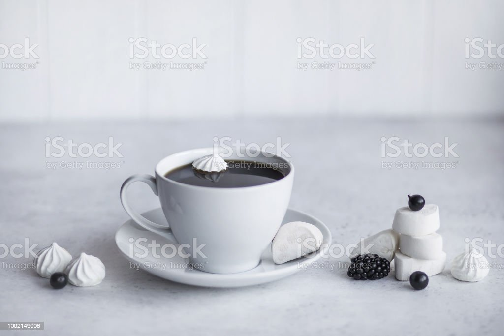 Cup of coffee, white background. Marshmallows, blue, black berries....
