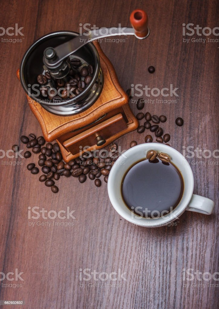A cup of coffee with a coffee grinder on a tree royalty-free stock photo