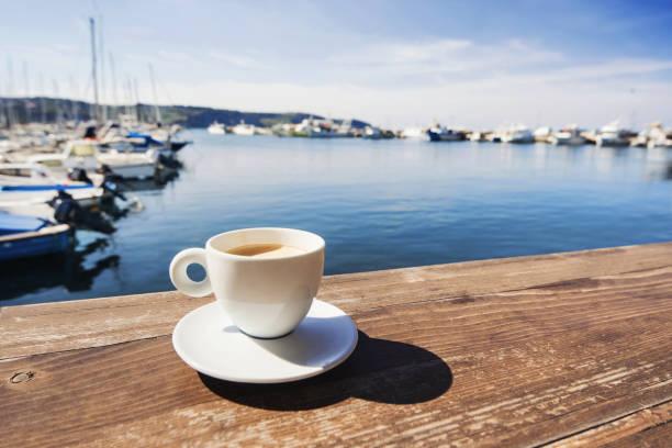 tasse kaffee mit einem meer im hintergrund - französische land tisch stock-fotos und bilder