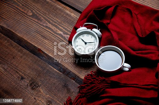 Cup of coffee with alarm clock and scarf on wooden table