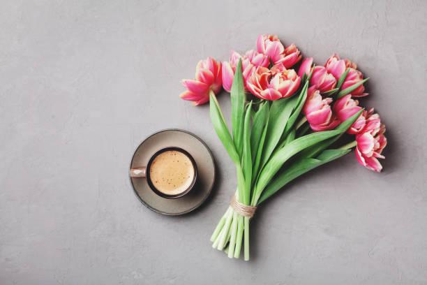 tasse de café avec des fleurs magnifiques tulipes roses. petit déjeuner le jour de mère ou de la femme. poser de plat. - tasse flat photos et images de collection