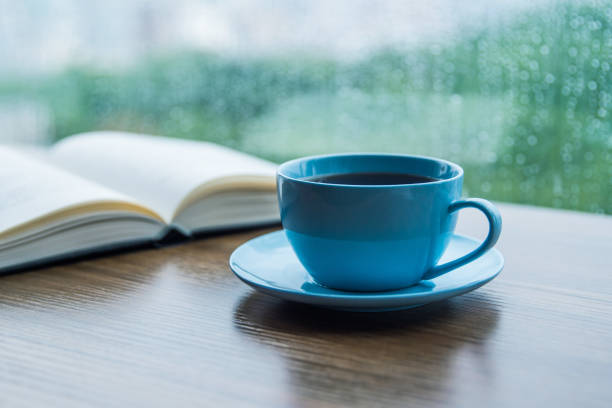 Tasse Kaffee mit Buch auf dem Tisch in Regentag – Foto