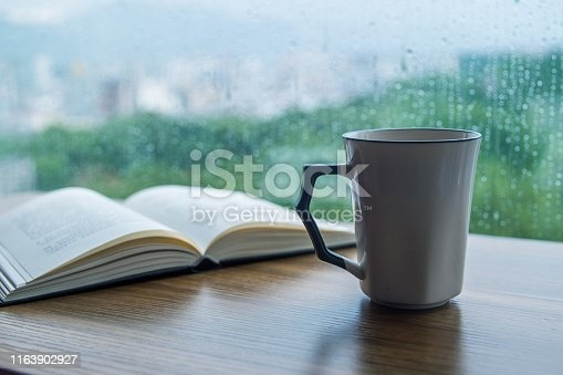 Cup of coffee with book on table in rain day