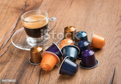 Berlin, Germany - January 23, 2015: Cup of Coffee with Nestle Nespresso Capsules on a wooden table