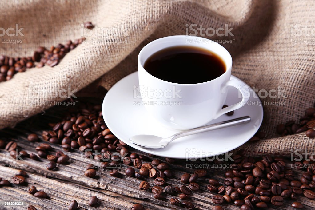 Cup of coffee with coffee beans on brown wooden background stock photo