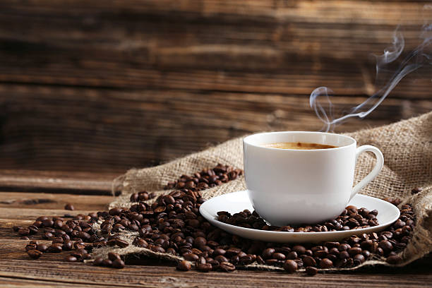 Cup of coffee with coffee beans Cup of coffee with coffee beans on a brown wooden background caffeine stock pictures, royalty-free photos & images